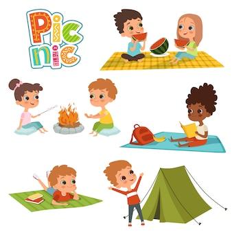 I bambini maschi e femmine si riposano sul picnic