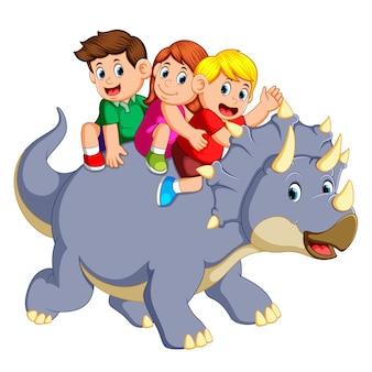I bambini sono seduti sul triceratopo e agitano la mano quando si muove