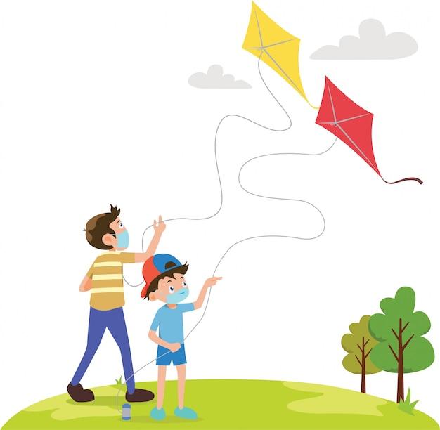 I fratelli giocano a kite insieme sul campo mentre usano la maschera medica