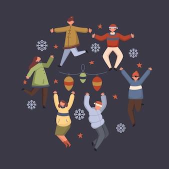 I giovani che indossano abiti invernali che salta insieme