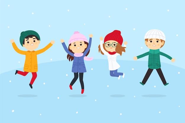 I giovani che indossano abiti invernali che saltano insieme