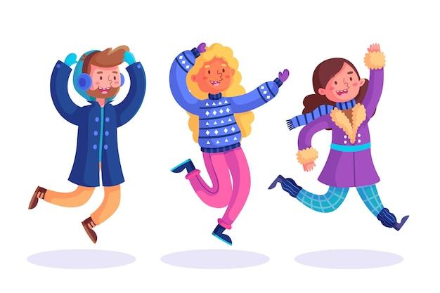 I giovani che indossano abiti invernali che saltano pack