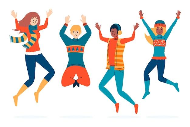 I giovani che indossano abiti invernali saltando