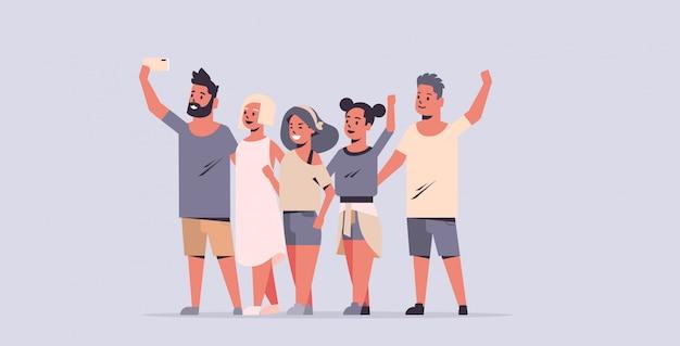 I giovani raggruppano la presa della foto del selfie sugli amici della macchina fotografica dello smartphone divertendosi i personaggi dei cartoni animati femminili maschii fondo orizzontale piano grigio integrale
