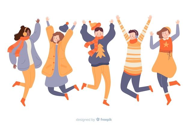 I giovani saltano mentre indossano abiti invernali