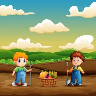 I ragazzi felici raccolgono la verdura su terreno agricolo