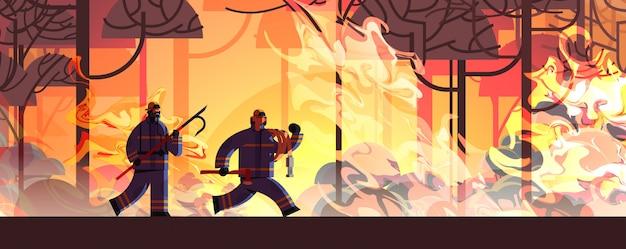 I vigili del fuoco coraggiosi con ascia di scarto e tubo estinguere i vigili del fuoco incendi pericolosi combattendo con cespuglio fuoco antincendio concetto di disastro naturale intenso arancione fiamme orizzontale