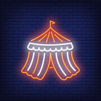 Icona al neon di tenda da circo. Fondo scuro a strisce della parete del mattone del domeon giusto.