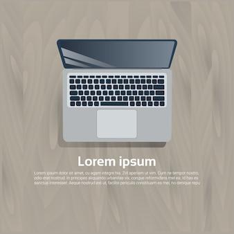 Icona di vista superiore del computer portatile sul fondo strutturato del modello di legno