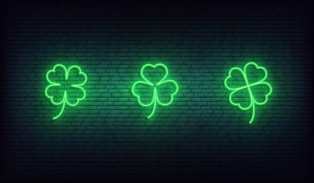 Icone al neon di trifoglio. insieme delle icone verdi dell'acetosella irlandese per il giorno di san patrizio