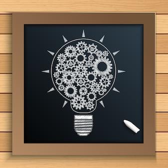 Idea della lampadina con gli ingranaggi scritti da gesso sulla lavagna