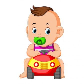 Il bambino divertente gioca felice con il giocattolo dell'auto