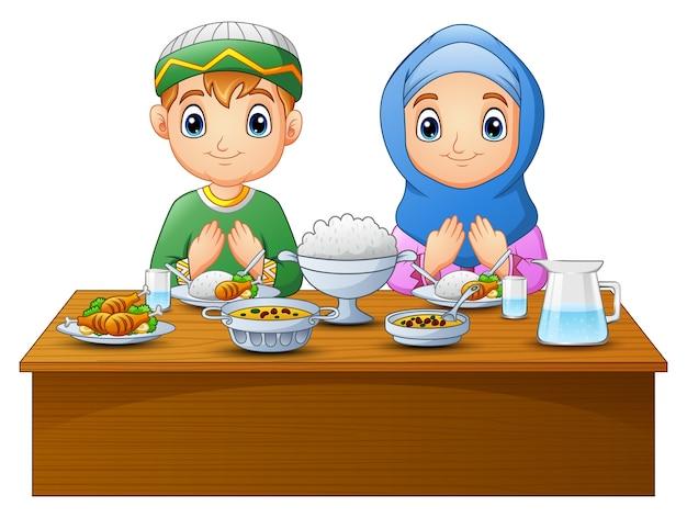 Il bambino musulmano prega insieme prima di rompere il digiuno