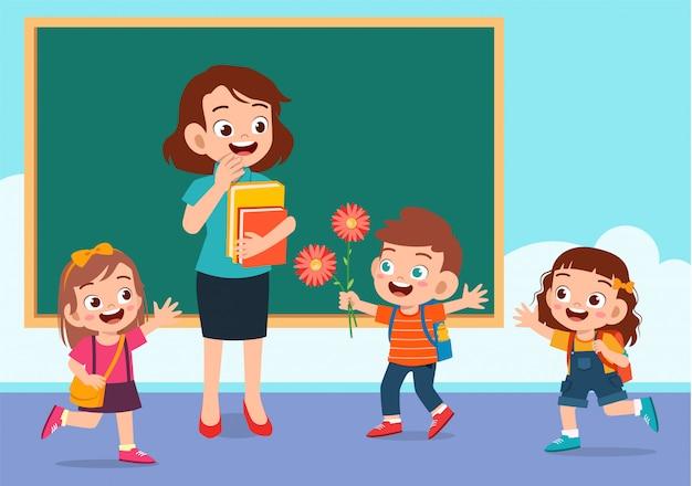 Il bambino sveglio felice dà il fiore all'insegnante