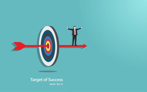 Il basamento felice dell'uomo d'affari sulla freccia penetra nel centro dell'obiettivo di successo