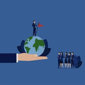 Il capo di affari sta sul globo superiore con la metafora dell'obiettivo di successo.