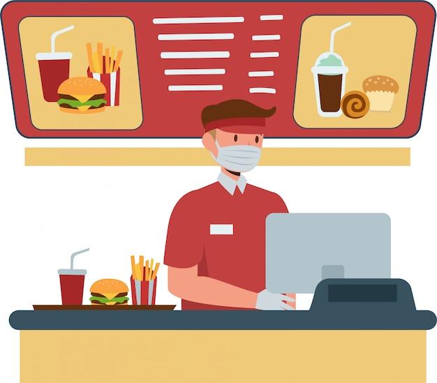 Il cassiere degli alimenti a rapida preparazione continua a utilizzare la maschera medica mentre si lavora sulla cassa del fast food