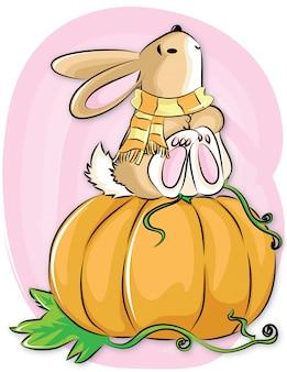 Il coniglio con l'abete si siede sui pumkins