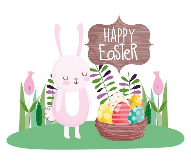 Il coniglio sveglio felice di pasqua con il canestro ha riempito i fiori della decorazione delle uova