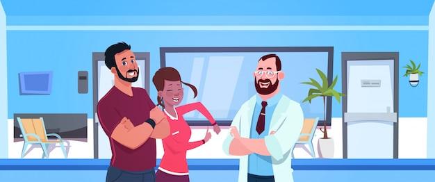 Il dottore talking with happy couple of patients sopra la sala di attesa dell'ospedale