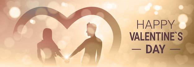 Il giorno felice di biglietti di s. valentino con le coppie tiene le mani sopra l'insegna orizzontale leggera brillante della sfuocatura dorata di bokeh