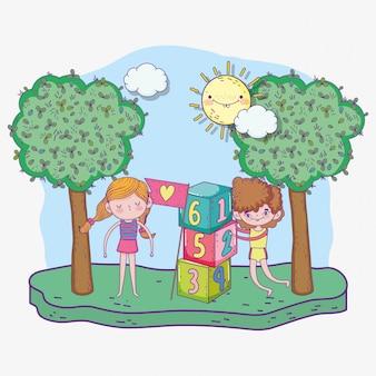 Il giorno, il ragazzo e la ragazza dei bambini felici che giocano con i blocchi di numeri parcheggiano