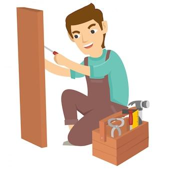 Il giovane carpentiere usa il trapano per fare un foro in legno