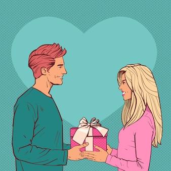 Il giovane dà il contenitore di regalo alla donna sopra il concetto del presente di festa di valentine day di forma del cuore