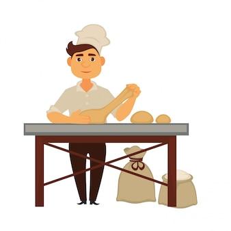 Il giovane fornaio impasta l'impasto e prepara delle pagnotte di pane