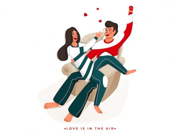 Il giovane ragazzo propone alla sua ragazza che si siede sul sofà perché l'amore è nel concetto dell'aria.