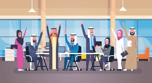Il gruppo di gente di affari araba allegra felice ha sollevato le mani che si siedono insieme alla riuscita della squadra dei lavoratori musulmani della scrivania