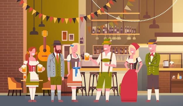 Il gruppo di persone beve la birra nell'uomo e nella donna di celebrazione del partito di oktoberfest della barra che indossano il concetto tradizionale del fest dei vestiti