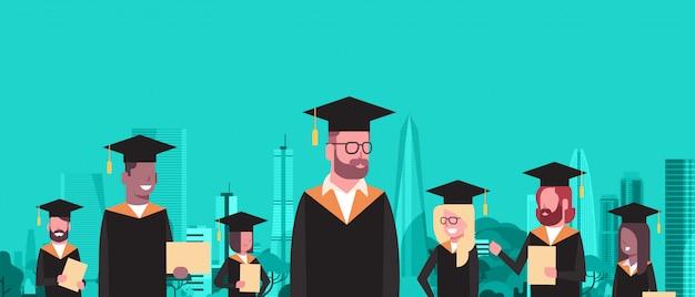 Il gruppo di studenti della corsa della miscela in laurea e abito tiene il diploma sopra gli edifici moderni della città