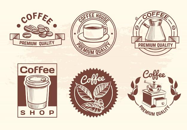Il logo disegnato a mano d'annata del caffè delle bevande calde ha messo con la tazza ed i fagioli