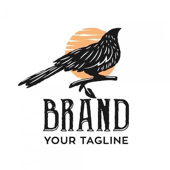 Il logo vintage di un corvo appollaiato nel pomeriggio