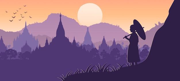 Il monaco tiene l'ombrello sulla scogliera e cerca il mare di pagoda a bagan