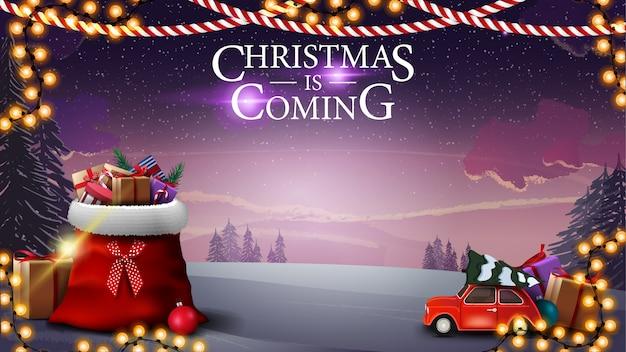 Il natale sta arrivando, biglietto di auguri con uno splendido paesaggio invernale, borsa di babbo natale con regali e macchina rossa vintage che trasporta l'albero di natale