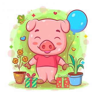 Il porcellino rosa sta vicino al dono e alle piante dell'illustrazione