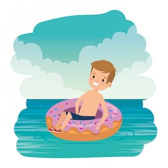 Il ragazzino sveglio con il costume da bagno e la ciambella galleggiano sul mare