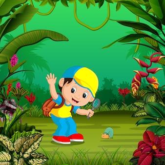 Il ragazzo allegro sta cercando una piccola lumaca