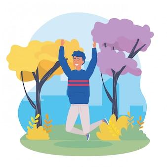 Il ragazzo che salta con gli abiti casual e gli alberi