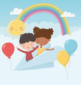 Il ragazzo e la ragazza del giorno dei bambini felici godono di con gli aerostati dell'aereo di carta