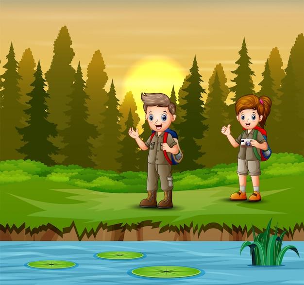 Il ragazzo e la ragazza scout riposano vicino al fiume