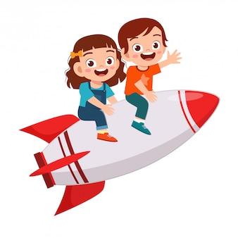 Il ragazzo e la ragazza svegli felici dei bambini guidano il razzo