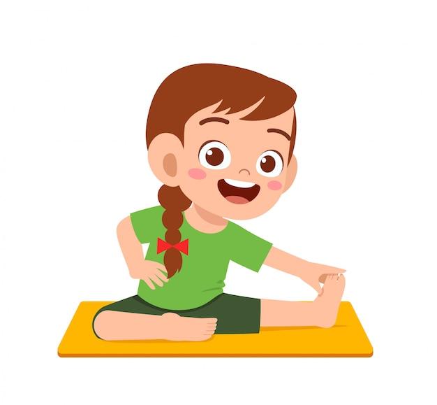 Il ragazzo e la ragazza svegli felici del bambino fanno la posa di yoga
