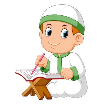 Il ragazzo è seduto e sta leggendo il corano