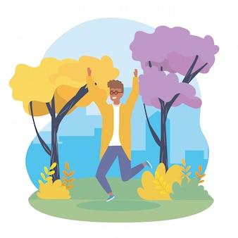Il ragazzo felice che salta con gli abiti casual e gli alberi
