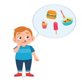 Il ragazzo grasso sveglio mangia gli alimenti industriali