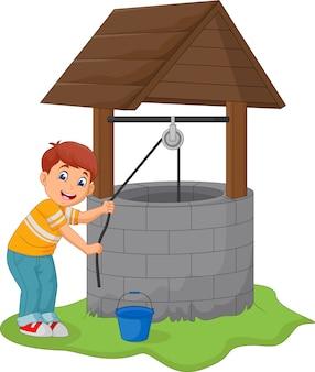 Il ragazzo prende l'acqua nel pozzo