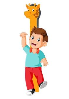Il ragazzo sta misurando con il corpo all'altezza della misura della giraffa
